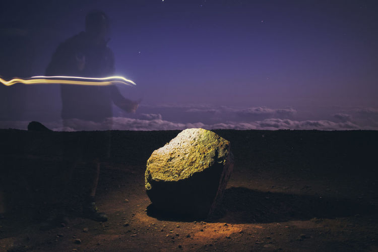 Silhouette person on rock by sea against sky at night