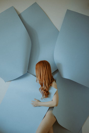 Side view of woman with blue papers standing against wall