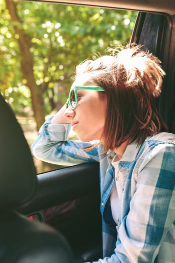 Young woman looking through window while traveling in car