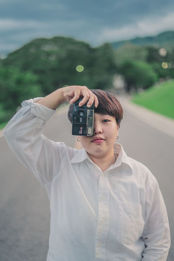 Young woman photographing with camera while standing on road