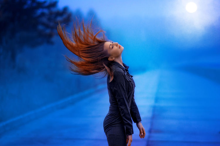 Side view of woman tossing hair while standing on road against sky at dusk