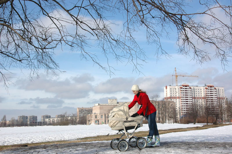 Woman With Baby Carriage On Street Against Building During Winter