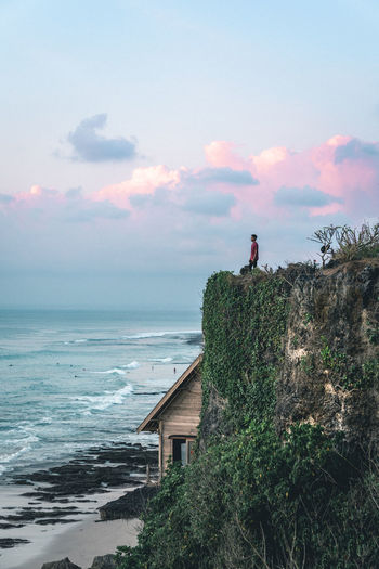 Young man standing alone on a big cliff watching sunset in Bali, Indonesia Bali Beach Photography INDONESIA Nature Pastel Sky Surf Beach Beauty In Nature Cliff Cloud - Sky Colorful Sky Horizon Over Water Nature One Person Outdoors Real People Scenics Sea Sky Sunset Tranquil Scene Tranquility Uluwatu Water Waves The Week On EyeEm The Traveler - 2018 EyeEm Awards Be Brave