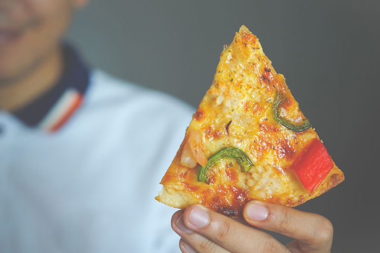 Man holding pizza Close-up Finger Focus On Foreground Food Food And Drink Freshness Hand Healthy Eating Holding Human Body Part Human Hand Indoors  Lifestyles Nacho Chip One Person Ready-to-eat Real People Snack Studio Shot Unrecognizable Person Wellbeing