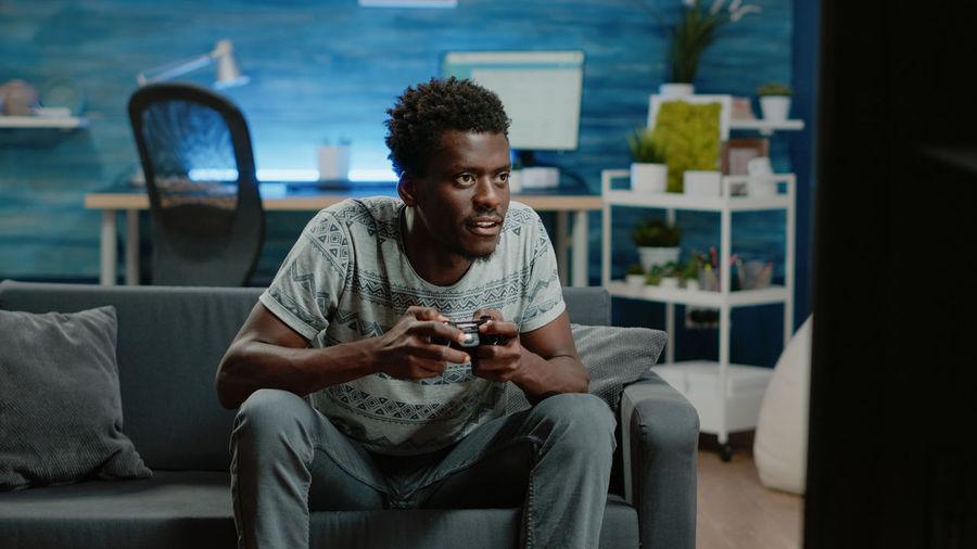 Young man looking at camera while sitting on sofa