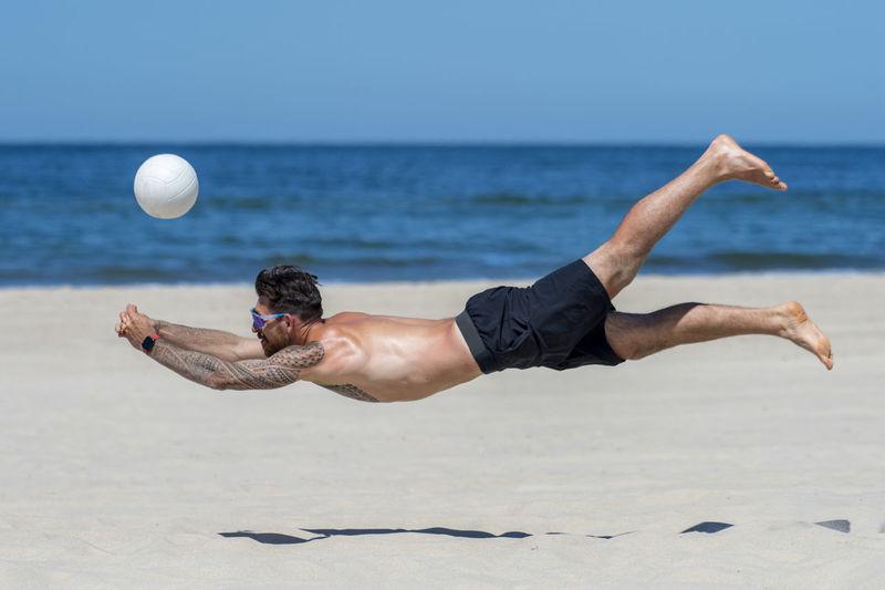 Shirtless man playing volleyball at beach