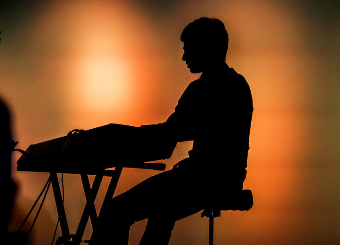 Silhouette man sitting on seat at music concert