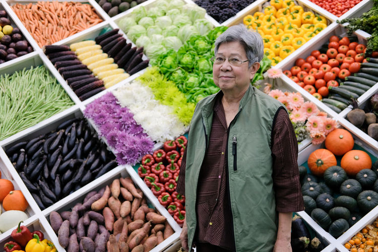 Portrait of senior woman standing at market stall