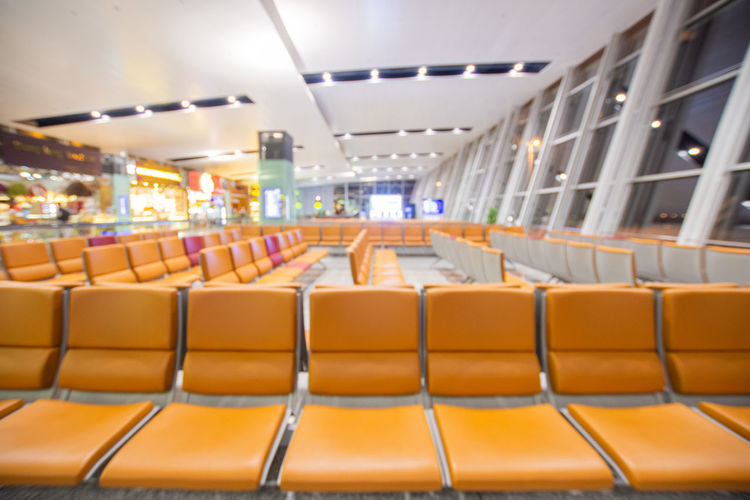 Seat Empty Chair Illuminated In A Row Absence Indoors  No People Transportation Side By Side Arts Culture And Entertainment Architecture Travel Lighting Equipment Arrangement Vehicle Seat Order Orange Color Auditorium Airport Ceiling