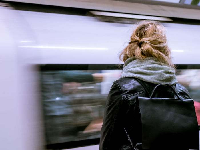 Rear view of woman standing against blur metro train at subway station
