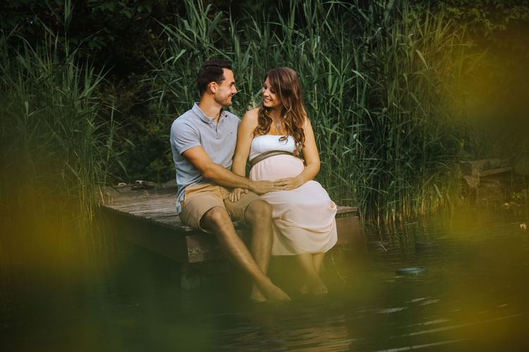 Man Kissing Pregnant Wife While Sitting On Pier Over Lake