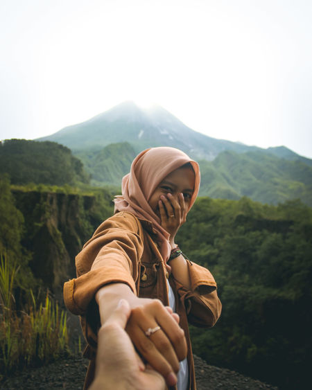 Cropped image of man holding woman hand against mountain ranges and sky