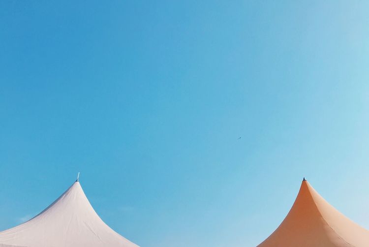 Low angle view of tents against clear blue sky