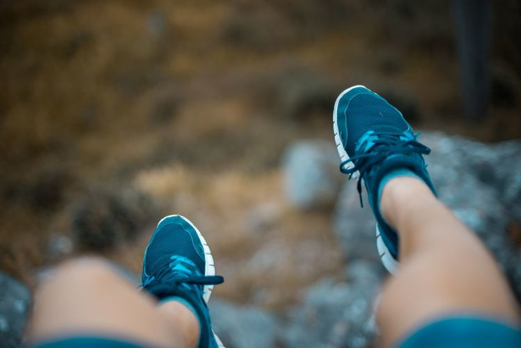 Low section of woman wearing shoes on cliff