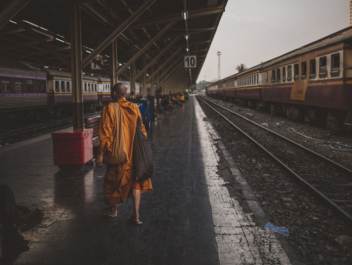Monk walking on railroad station platform