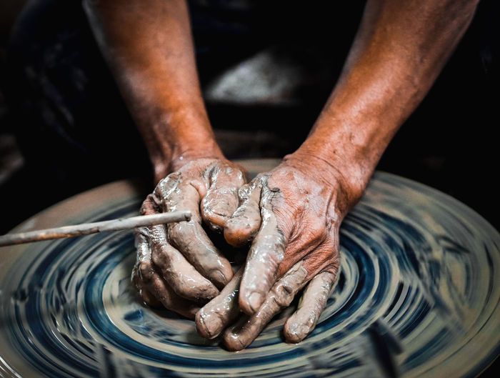 Cropped hands of man molding shape on pottery wheel
