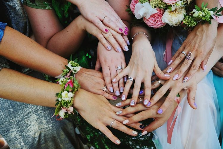 Midsection Of Friends And Bride Joining Hands At Wedding