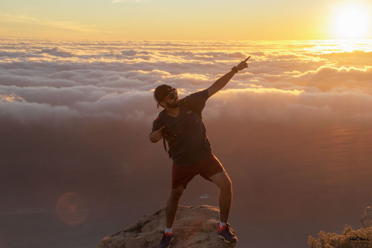 Full length of hiker posing while standing on rock against cloudscape