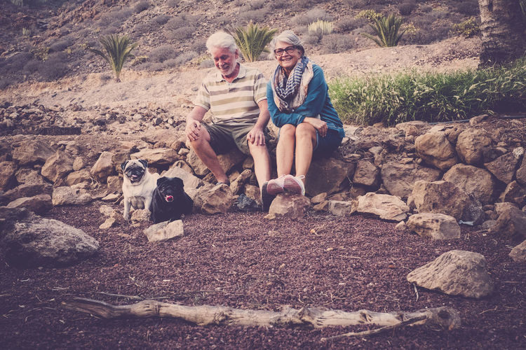 senior couple with grey hair sitting outdoor with pug dogs couple Pug Carlino Adult Bonding Day Family Portrait With Dogs Friendship Full Length Happiness Leisure Activity Lifestyles Nature Outdoors People Pug Dogs Couple Real People Relaxing Moments Senior Couple Sitting Smiling Togetherness Two People