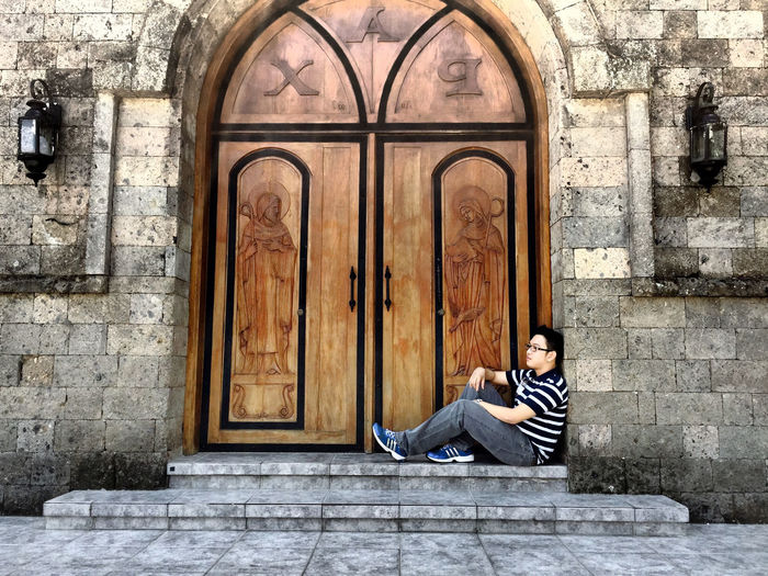 Man sitting by door of church