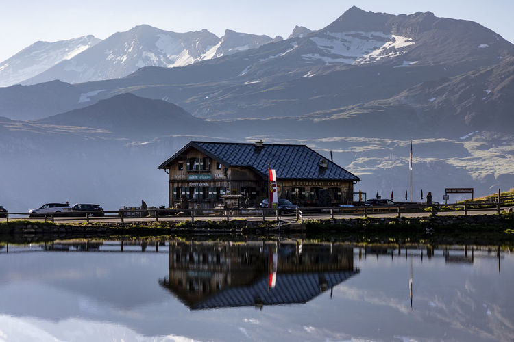 Reflection of house on lake by mountains against sky