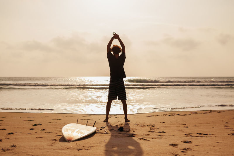 Surfer Exercising On Sand Against Sky During Sunset