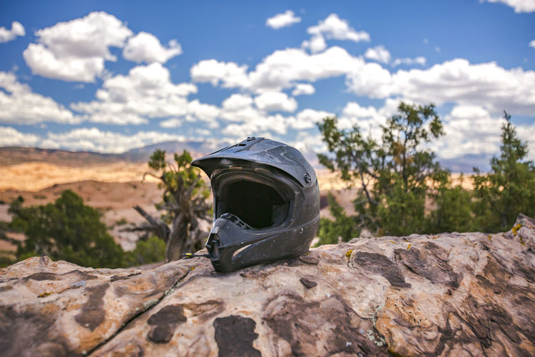 Close up of crash helmet on rock against sky