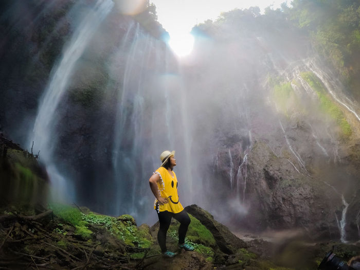 Activity Beauty In Nature Day Flowing Water Fog Forest Full Length Hiking Land Leisure Activity Lifestyles Mountain Nature One Person Outdoors Real People Rear View Scenics - Nature Standing Waterfall Yellow