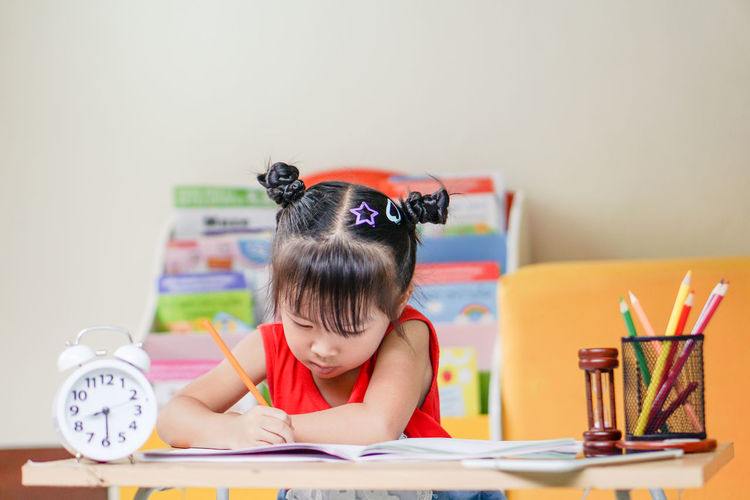 Cute girl drawing on paper while sitting on table at home