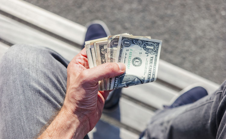 man sits on a bench and holding dollar notes Adult Adults Only American Bench Budget Currency Dollar Bill Hands Holding Hands Man Sitting Body Part Close-up Day Dollar Dollar Notes Dollars Finance Finance And Economy Holding Investment Make Money Paper Currency Shoes Sitting Alone