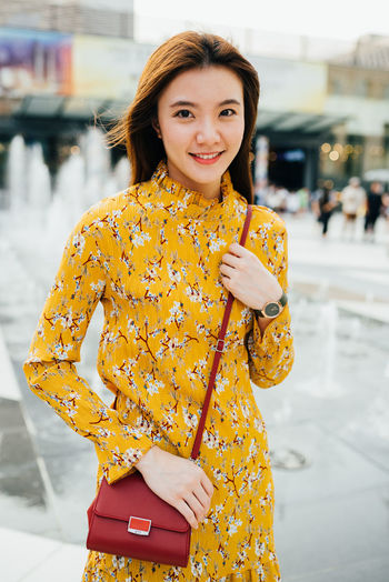 Portrait of smiling woman holding yellow while standing outdoors