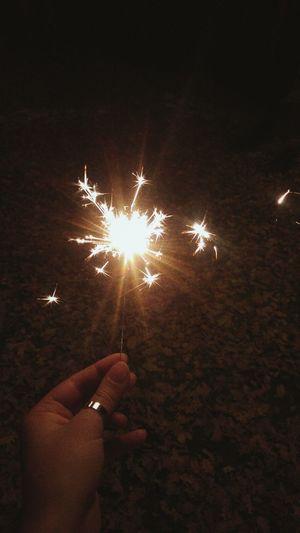 Close-up of hands over illuminated firework display at night