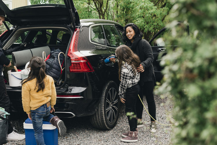 Full length of woman with children in car