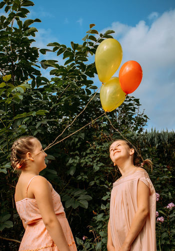 Two sisters in pink dresses and with balls tied to their braided hair are standing outside