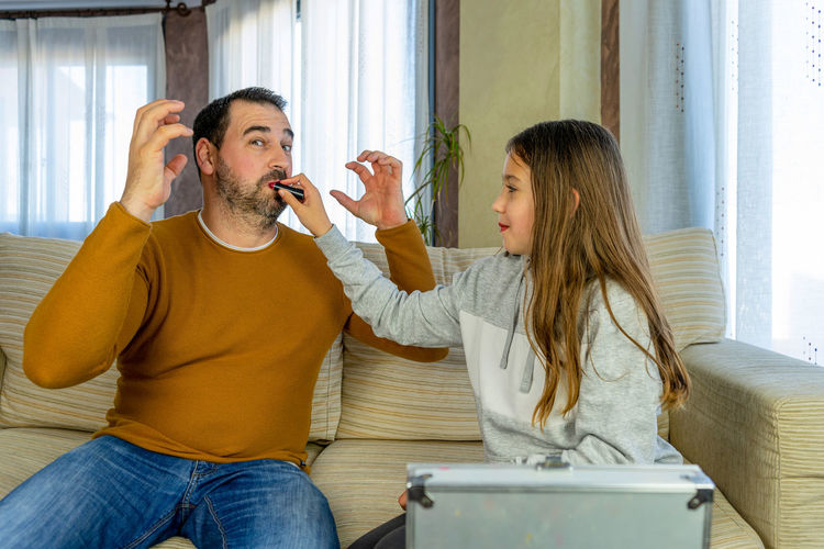 Man and woman using phone while sitting at home