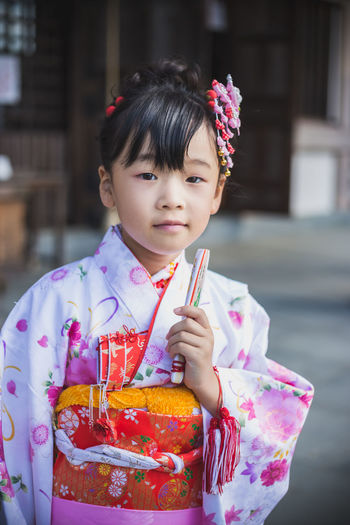 Close-Up Portrait Of Girl Wearing Kimono Outdoors