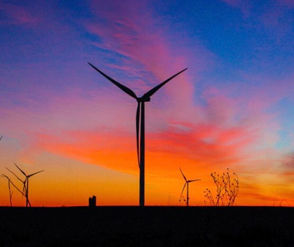 Low angle view of silhouette windmill against sky during sunset