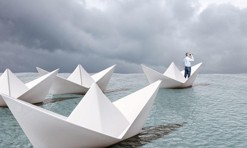 Men floating on sea against sky