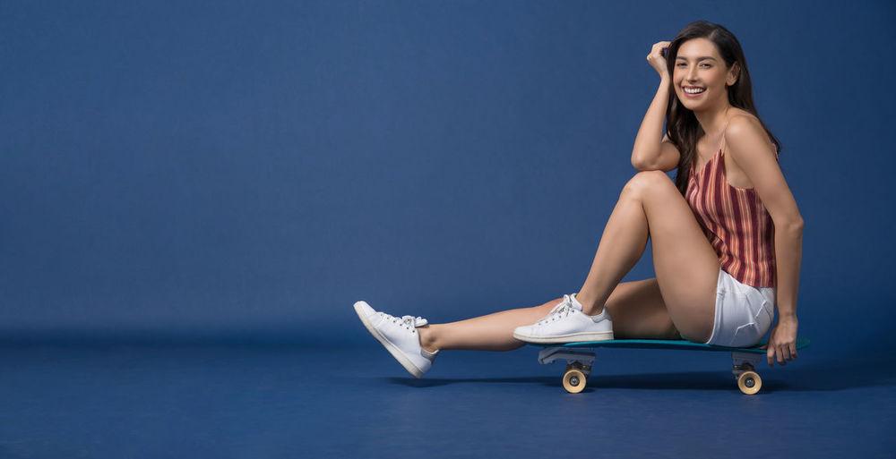 Portrait of woman sitting against blue background