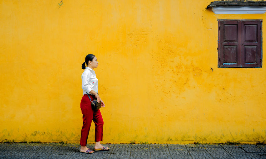 Side view of young woman standing on road against wall