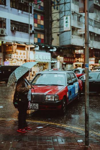 Full length of wet street in city during rainy season