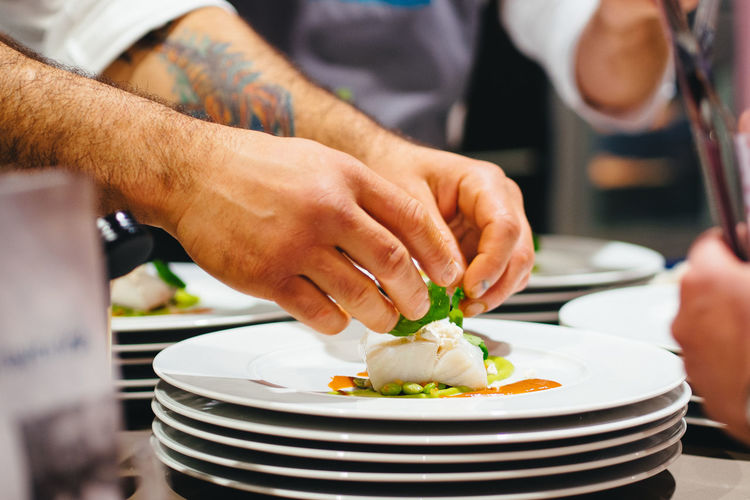 Cropped image of chef preparing seafood in plate at restaurant