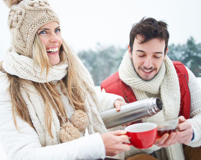 portrait of smiling young woman with ice cream in winter Adult Break Clothing Cold Temperature Couple Cup Drink Drinking Emotion Enjoy Enjoyment Feel Good Holiday Hot Hot Drink Infuse Jug Leisure Activity Lifestyles Love Man Mug On The Way Outdoors Outside People Pouring Real People Refreshment Relaxation Scarf Smiling Tea TeaCup Thermos Jug Thirst Trip Two People Warm Clothing Winter Winter Holiday Woman Women Young Adult Young Women