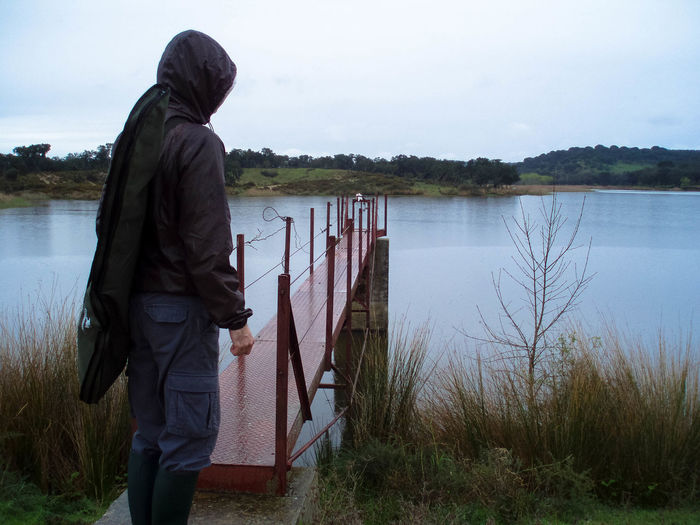 Rear view of man in hooded jacket standing by pier over lake