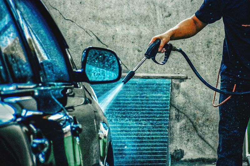 Midsection of man washing car with hose