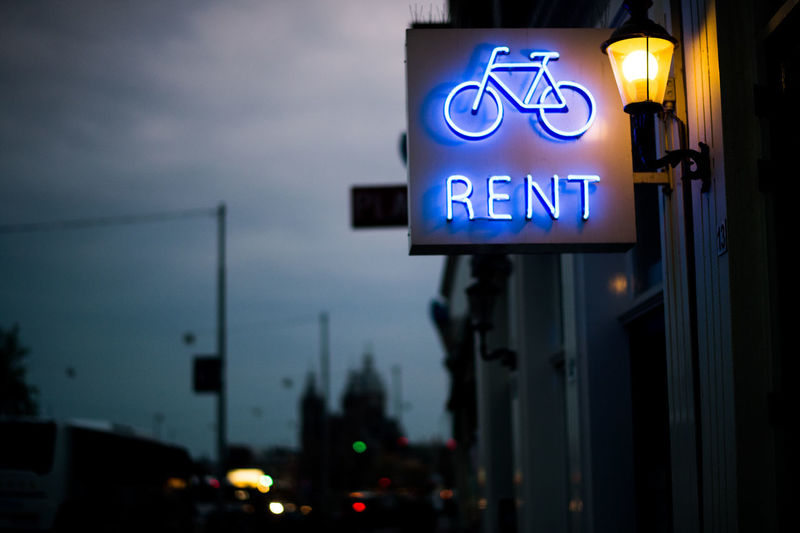 city of bicycles. Close-up Communication Cycle Rent Focus On Foreground Guidance Illuminated Neon Sign Night No People Outdoors RENT Road Sign Sky Text Transportation