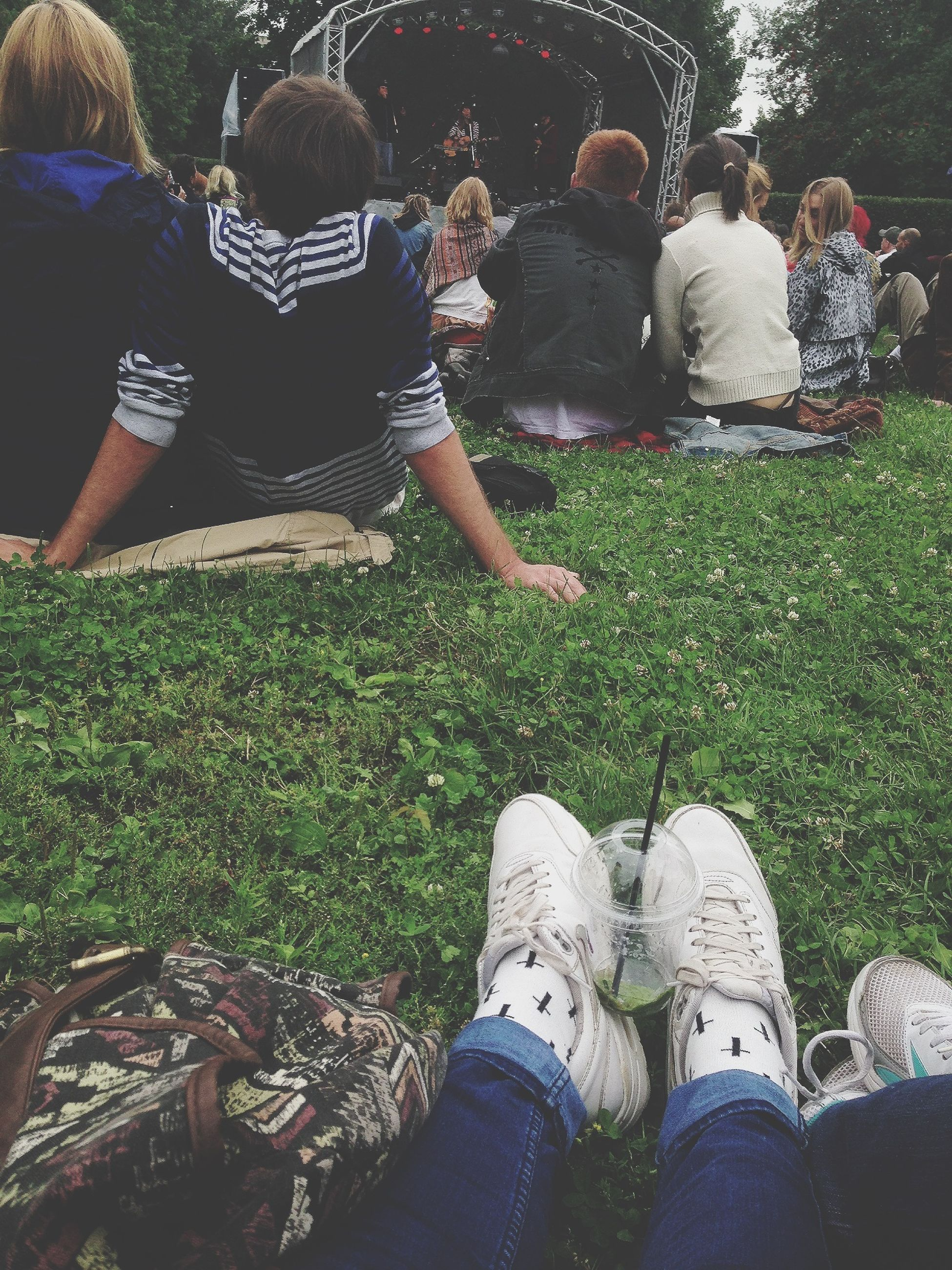 low section, lifestyles, leisure activity, grass, person, men, shoe, casual clothing, standing, togetherness, field, sitting, friendship, bonding, relaxation, grassy