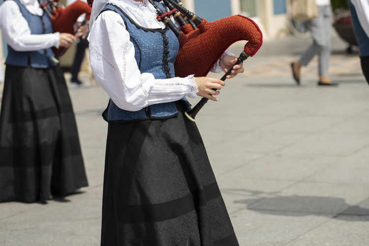 Woman playing bagpipe, spanish traditional dance group Asturias Hands Holiday Horizontal SPAIN Traditional Clothing Woman Bagpipe Costume Day Folk Folklore Lifestyles Music Musical Instrument Outdoors Performance Playing Real People Street Sunlight Traditional