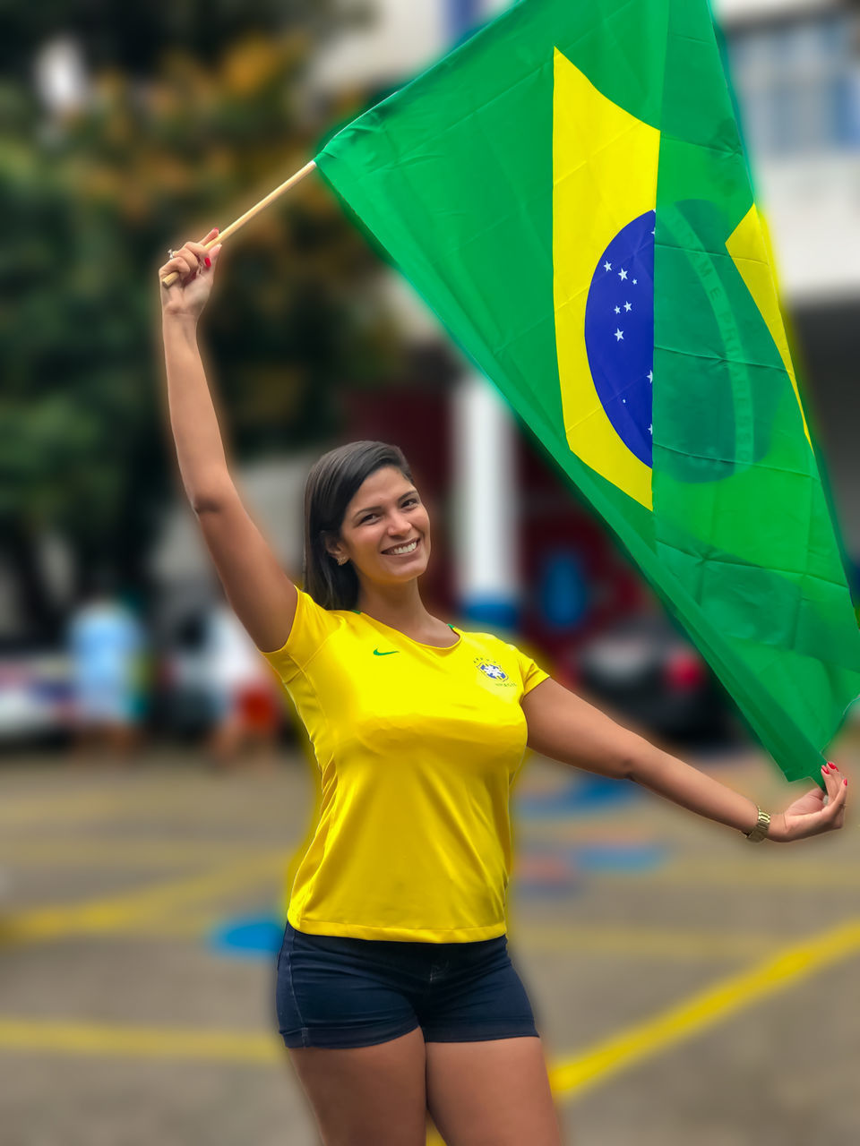 yellow, happiness, women, real people, lifestyles, emotion, focus on foreground, one person, smiling, multi colored, day, adult, leisure activity, young women, young adult, holding, motion, outdoors, front view, freedom, human arm, flag
