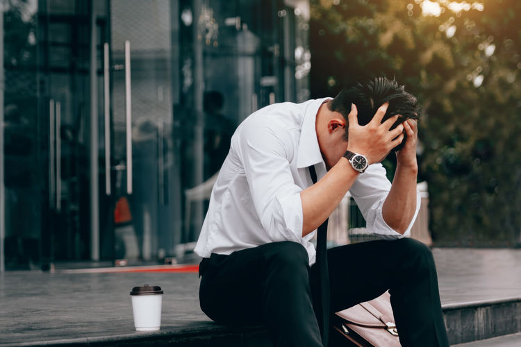 Stressed businessman with head in hands sitting on steps